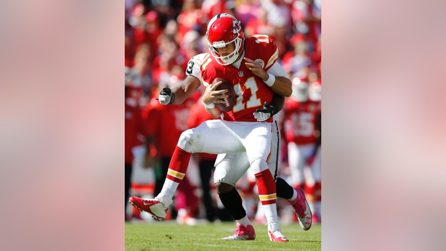 Kansas City Chiefs quarterback Alex Smith (11) is sacked by Oakland Raiders middle linebacker Nick Roach (53) during the first half of an NFL football game at Arrowhead Stadium in Kansas City, Mo., Sunday, Oct. 13, 2013. (AP Photo/Ed Zurga)