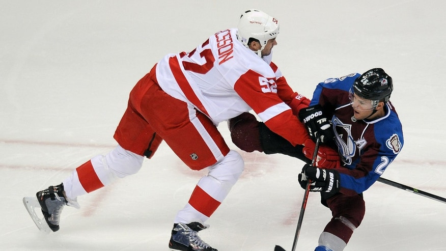 Detroit Red Wings defenseman Jonathan Ericsson, left, of Sweden, checks Colorado Avalanche center Paul Stastny as Stastny passes the puck in the first period of an NHL hockey game Thursday, Oct. 17, 2013, in Denver. (AP Photo/Chris Schneider)