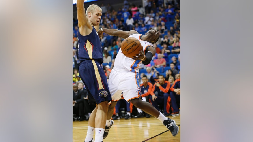 Oklahoma City Thunder guard Reggie Jackson, right, is fouled by New Orleans Pelicans center Greg Stiemsma during the third quarter of an NBA basketball preseason game in Tulsa, Okla., Thursday, Oct. 17, 2013. New Orleans won 105-102. (AP Photo/Sue Ogrocki)