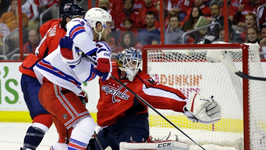 New York Rangers right wing Ryan Callahan, center, scores a goal past Washington Capitals goalie Braden Holtby, right, in the second period of an NHL hockey game, Wednesday, Oct. 16, 2013, in Washington. (AP Photo/Alex Brandon)