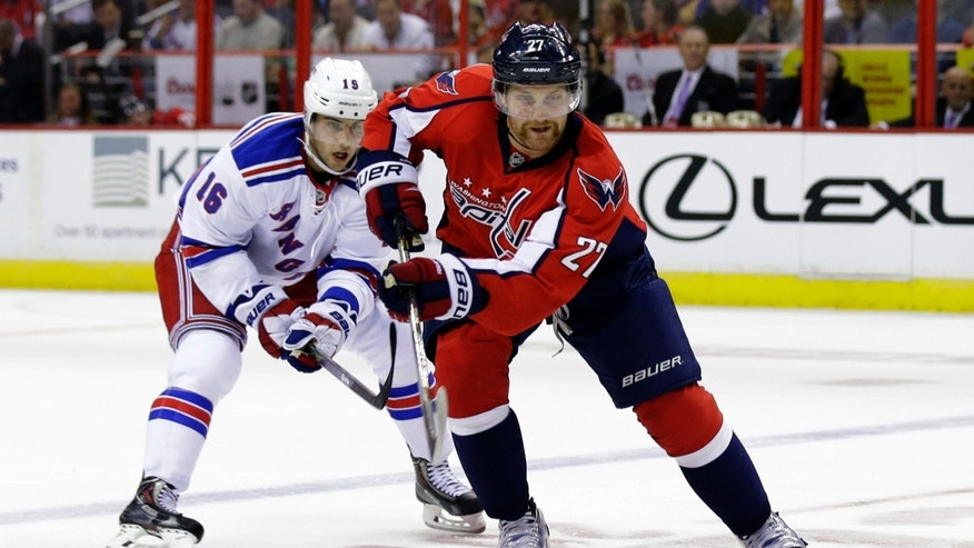 Washington Capitals defenseman Karl Alzner, right, skates with the puck with New York Rangers center Derick Brassard, behind, in the first period of an NHL hockey game, Wednesday, Oct. 16, 2013, in Washington. (AP Photo/Alex Brandon)