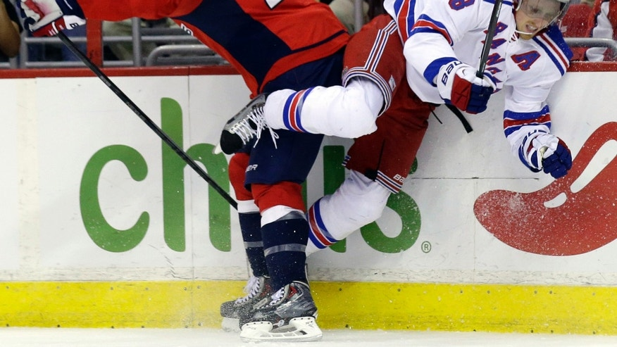 Washington Capitals right wing Troy Brouwer, left, boards New York Rangers defenseman Marc Staal in the first period of an NHL hockey game, Wednesday, Oct. 16, 2013, in Washington. (AP Photo/Alex Brandon)