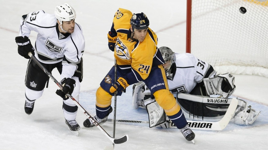 Los Angeles Kings defenseman Willie Mitchell (33) and Nashville Predators forward Eric Nystrom (24) watch as the puck is deflected past them in the first period of an NHL hockey game Thursday, Oct. 17, 2013, in Nashville, Tenn. Kings goalie Jonathan Quick (32) guards the net. (AP Photo/Mark Humphrey)
