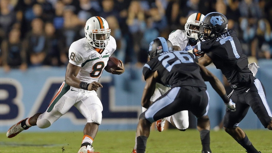 Miami's Duke Johnson (8) runs the ball as North Carolina's Dominique Green (26) and Tim Scott (7) move in to attempt the tackle during the first half of an NCAA college football game in Chapel Hill, N.C., Thursday, Oct. 17, 2013. (AP Photo/Gerry Broome)