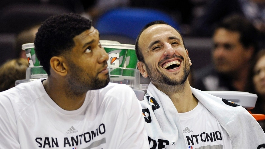 San Antonio Spurs' Manu Ginobili, right, of Argentina, laughs with teammate Tim Duncan on the bench during the second half of an NBA preseason basketball game against the Phoenix Suns, Sunday, Oct. 13, 2013, in San Antonio. Phoenix won 106-99. (AP Photo/Darren Abate)