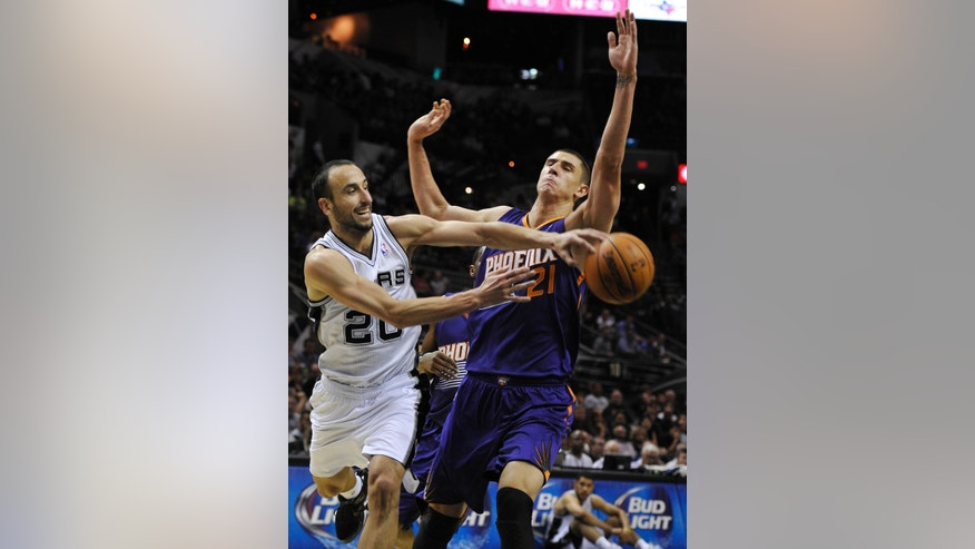 San Antonio Spurs' Manu Ginobili, left, of Argentina, passes in front of Phoenix Suns' Alex Len during the first half of an NBA preseason basketball game on Sunday, Oct. 13, 2013, in San Antonio. (AP Photo/Darren Abate)