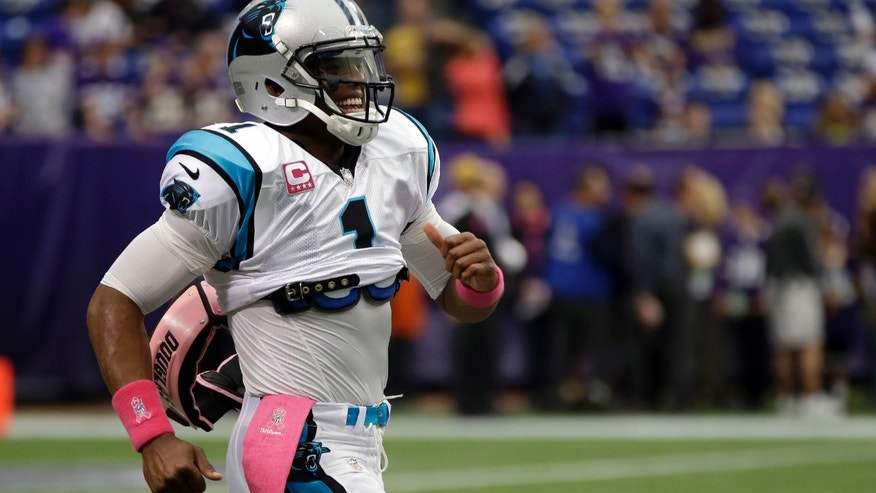Carolina Panthers quarterback Cam Newton smiles as he runs down field as he warms up before an NFL football game against the Minnesota Vikings in Minneapolis, Sunday, Oct. 13, 2013. (AP Photo/Jim Mone)