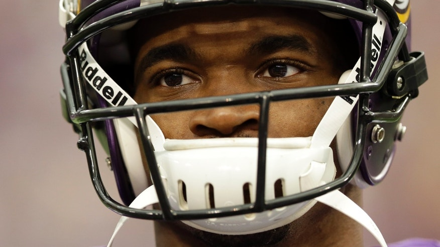 Minnesota Vikings running back Adrian Peterson pauses during introductions before an NFL football game against the Carolina Panthers in Minneapolis, Sunday, Oct. 13, 2013. One of the star running back's sons, a 2-year-old in South Dakota, died Friday after an alleged attack in a child abuse case. (AP Photo/Michael Conroy)