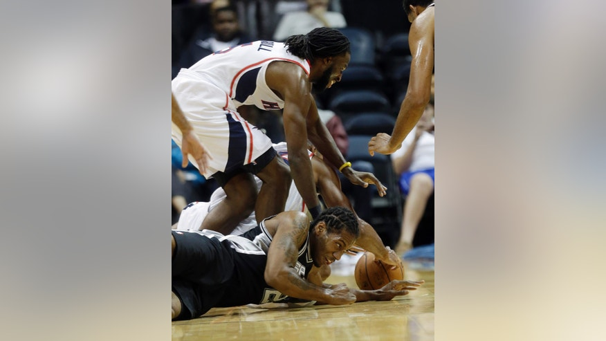 San Antonio Spurs small forward Kawhi Leonard (2) on floor, and Atlanta Hawks small forward DeMarre Carroll (5) battle for a loose ball half of a preseason NBA basketball game, Thursday, Oct. 17, 2013 in Atlanta. (AP Photo/John Bazemore)
