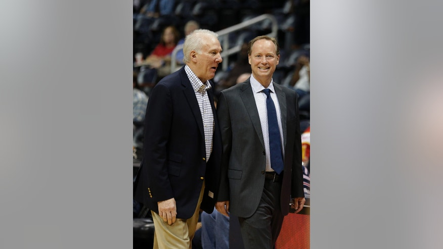 Atlanta Hawks head coach Mike Budenholzer, right, talks with San Antonio Spurs head coach Gregg Popovich before a preseason NBA basketball game, Thursday, Oct. 17, 2013 in Atlanta. Budenholzer was an assistant coach in San Antonio for 19 years before getting the Hawks' head coaching job. (AP Photo/John Bazemore)