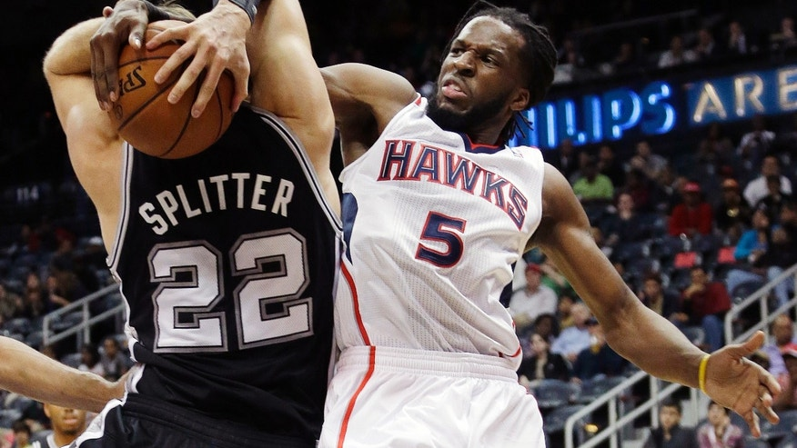 San Antonio Spurs power forward Tiago Splitter (22) and Atlanta Hawks small forward DeMarre Carroll (5) fight for a rebound in the first half of a preseason NBA basketball game, Thursday, Oct. 17, 2013 in Atlanta. (AP Photo/John Bazemore)