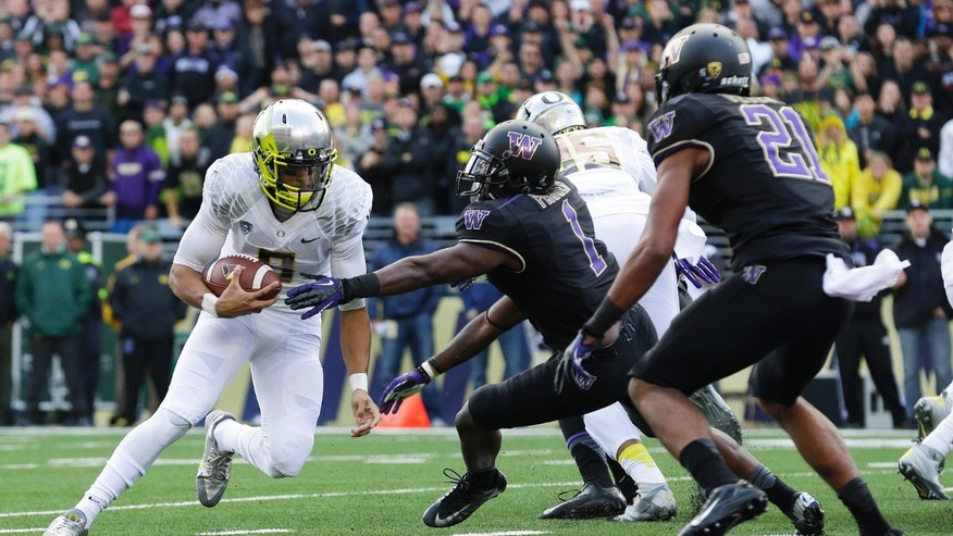 Oregon quarterback Marcus Mariota, left, runs the ball on a keeper play against Washington in the first half of an NCAA college football game, Saturday, Oct. 12, 2013, in Seattle. Mariota was stopped short of the goal line, but Oregon scored a touchdown on the next play. (AP Photo/Ted S. Warren)