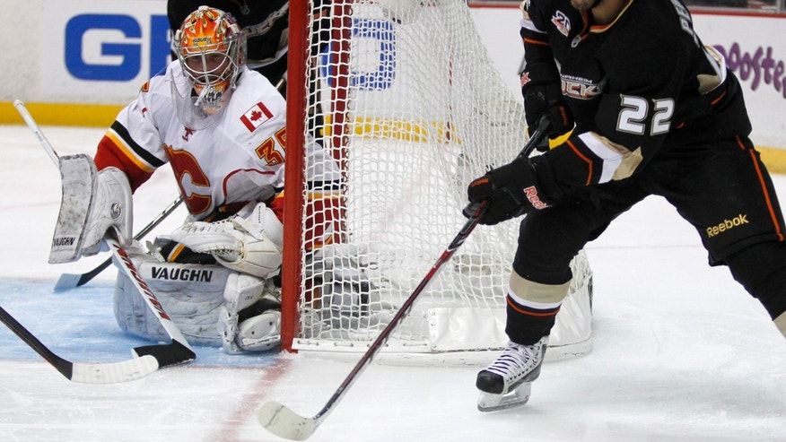 Anaheim Ducks center Mathieu Perreault (22) takes the puck around the net with Calgary Flames goalie Joey MacDonald (35) defending during the second period of an NHL hockey game, Wednesday, Oct. 16, 2013, in Anaheim, Calif. (AP Photo/Alex Gallardo)
