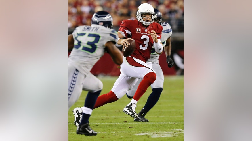 Arizona Cardinals quarterback Carson Palmer (3) scrambles under pressure from Seattle Seahawks outside linebacker Malcolm Smith (53) during the first half of an NFL football game, Thursday, Oct. 17, 2013, in Glendale, Ariz. (AP Photo/Ross D. Franklin)