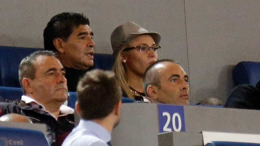 Argentine's former soccer star Diego Armando Maradona, top left,  follows a Serie A soccer match between AS Roma and Napoli at Rome's Olympic stadium, Friday, Oct. 18, 2013.  Italy's tax collection agency says it has formally notified Diego Maradona that it will begin procedures to freeze his assets in Italy to pay off his tax debt of $53 million. Equitalia confirmed news reports Friday saying its agents had served Maradona with the notification in his Milan hotel room, and that he signed the documentation. (AP Photo/Gregorio Borgia)