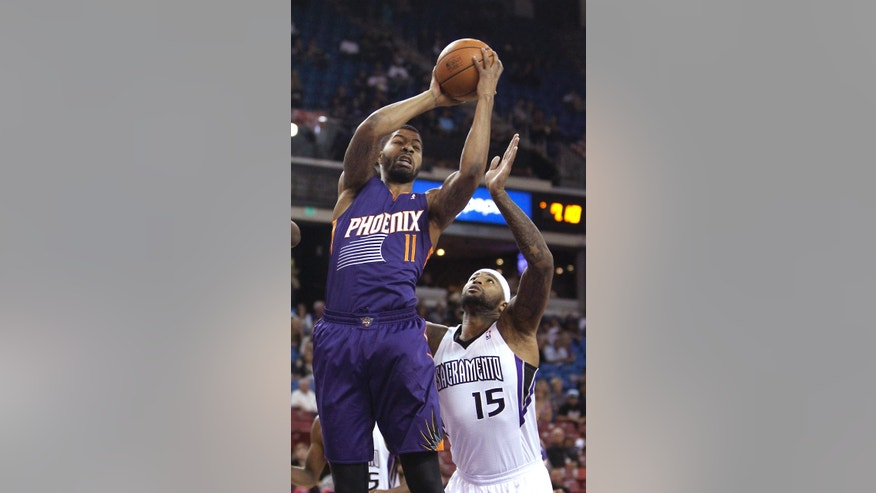Phoenix Suns forward Markieff Morris, left, grabs a rebound over Sacramento Kings center DeMarcus Cousins during the first quarter of an NBA preseason basketball game in Sacramento, Calif., Thursday, Oct. 17, 2013. (AP Photo/Rich Pedroncelli)