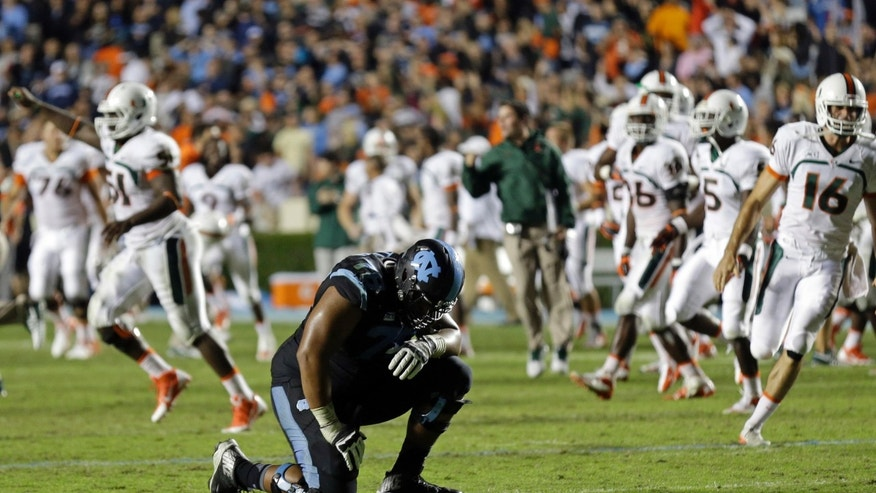 North Carolina's Landon Turner (78) kneels following North Carolina's loss to Miami in an NCAA college football game in Chapel Hill, N.C., Thursday, Oct. 17, 2013. Miami won 27-23. (AP Photo/Gerry Broome)