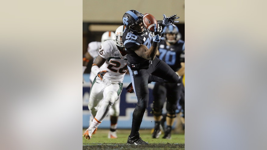 Miami's Rayshawn Jenkins (26) chases North Carolina's Eric Ebron (85) as Ebron reaches for a pass during the second half of an NCAA college football game in Chapel Hill, N.C., Thursday, Oct. 17, 2013. Miami won 27-23. (AP Photo/Gerry Broome)