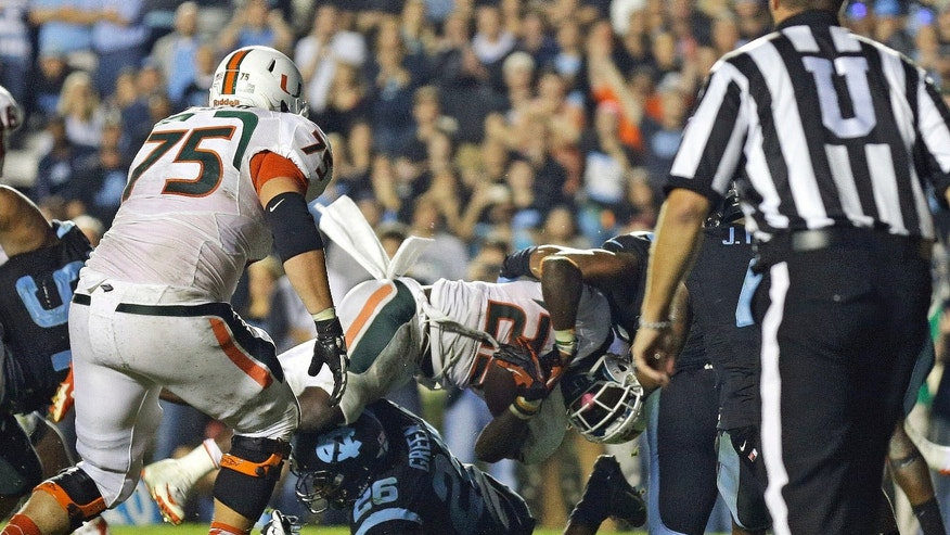 Miami's Dallas Crawford (25) dives into the end zone for the winning touchdown as North Carolina's Dominique Green (26) tries to make the stop during the second half of an NCAA college football game in Chapel Hill, N.C., Thursday, Oct. 17, 2013.  Miami won 27-23. (AP Photo/Gerry Broome)