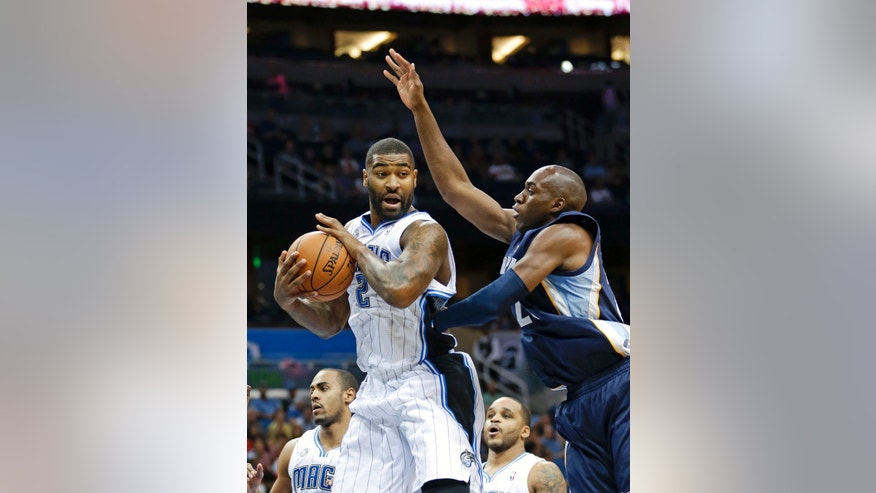 Orlando Magic's Kyle O'Quinn, left, grabs a rebound in front of Memphis Grizzlies' Quincy Pondexter, right, during the first half of an NBA preseason basketball game in Orlando, Fla., Friday, Oct. 18, 2013.(AP Photo/John Raoux)