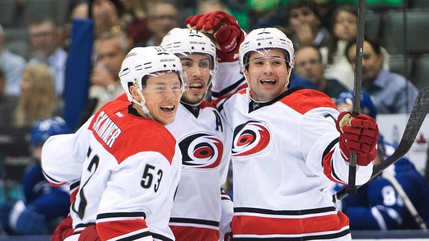 Carolina Hurricanes defenseman Ryan Murphy, right, celebrates his goal with teammates Jeff Skinner, left, and Justin Faulk against the Toronto Maple Leafs during the third period of an NHL hockey game in Toronto on Thursday, Oct. 17, 2013. (AP Photo/The Canadian Press, Nathan Denette)