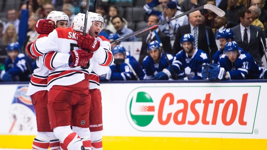 Carolina Hurricanes defenseman Ryan Murphy, right, celebrates his goal with teammates Jeff Skinner, centcer, and Justin Faulk against the Toronto Maple Leafs during the third period of an NHL hockey game in Toronto on Thursday, Oct. 17, 2013. (AP Photo/The Canadian Press, Nathan Denette)