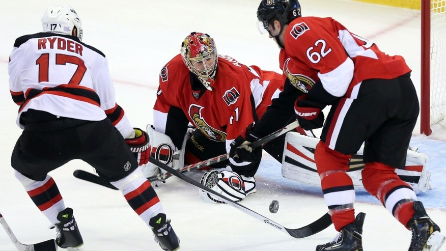 Ottawa Senators goaltender Craig Anderson, center, keeps his eye on the loose puck as teammate Eric Gryba, right, and New Jersey Devils' Michael Ryder battle in front of the net during the first period of an NHL hockey game Thursday, Oct. 17, 2013, in Ottawa, Ontario. (AP Photo/The Canadian Press, Fred Chartrand)