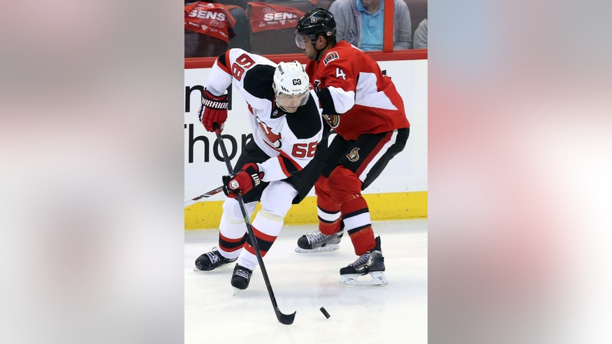New Jersey Devils' Jaromir Jagr, left, takes possession of the puck from Ottawa Senators' Chris Phillips during the first period of an NHL hockey game Thursday, Oct. 17, 2013, in Ottawa, Ontario. (AP Photo/The Canadian Press, Fred Chartrand)