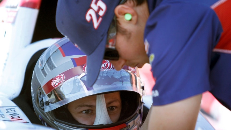 Marco Andretti sits in his car as a crew member makes adjustments, during a practice session for Saturday's IndyCar auto race, Friday, Oct. 18, 2013, at Auto Club Speedway in Fontana, Calif. (AP Photo/Alex Gallardo)