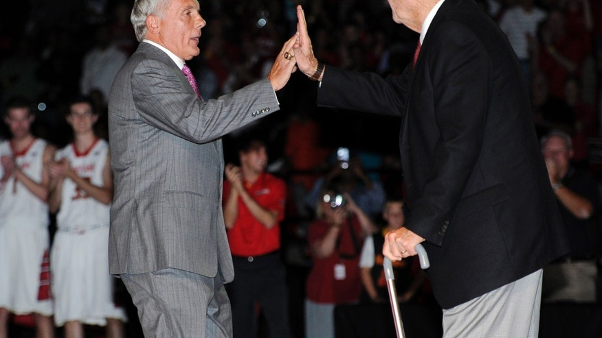 Former Maryland men's basketball coaches Gary Williams, left, and Lefty Driesell high-five during Maryland Madness college basketball events, Friday, Oct. 18, 2013, in College Park, Md. (AP Photo/Nick Wass)