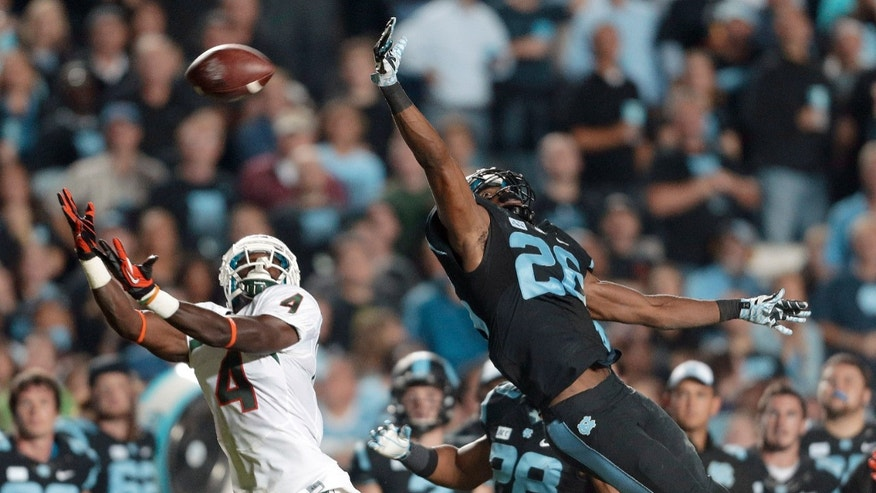 Miami's Phillip Dorsett (4) reaches for a pass as North Carolina's Dominique Green (26) defends during the first half of an NCAA college football game in Chapel Hill, N.C., Thursday, Oct. 17, 2013. The pass was complete. (AP Photo/Gerry Broome)