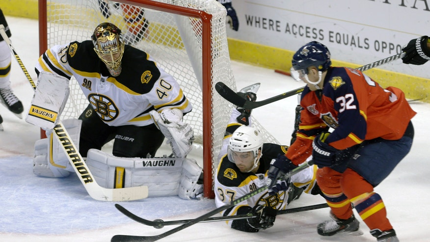 Boston Bruins goalie Tuukka Rask (40) prepares to stop a shot by Florida Panthers right wing Kris Versteeg (32) in the second  period of an NHL hockey  game as Patrice Bergeron (37) defends, Thursday, Oct. 17, 2013, in Sunrise, Fla. (AP Photo/Alan Diaz)
