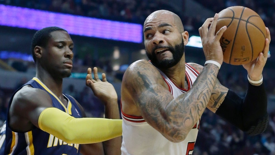 Chicago Bulls forward Carlos Boozer (5) looks to the basket as Indiana Pacers center Ian Mahinmi (28) guards during the first half of an NBA preseason basketball game in Chicago on Friday, Oct. 18, 2013. (AP Photo/Nam Y. Huh)