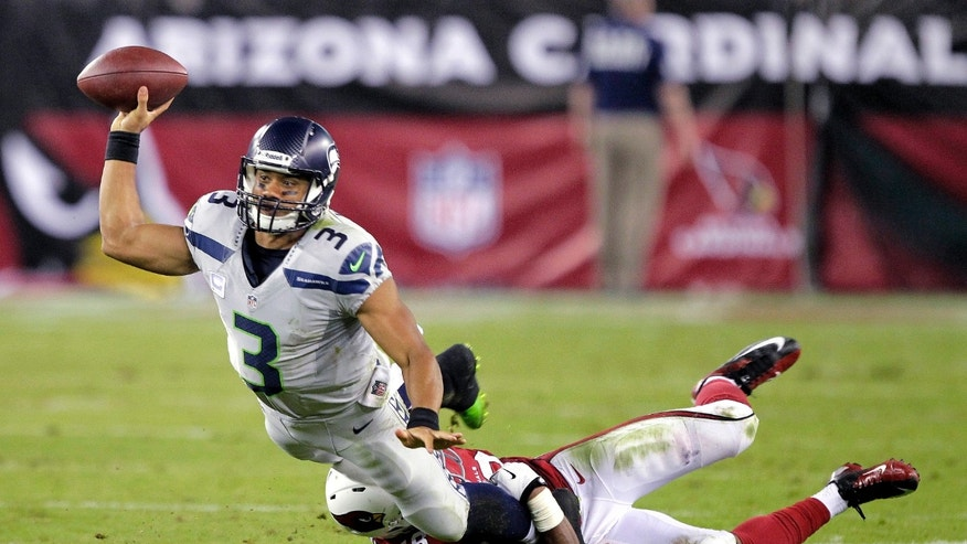 Seattle Seahawks quarterback Russell Wilson (3) gets a pass off as Arizona Cardinals inside linebacker Karlos Dansby (56) brings him down during the second half of an NFL football game, Thursday, Oct. 17, 2013, in Glendale, Ariz. (AP Photo/Rick Scuteri)