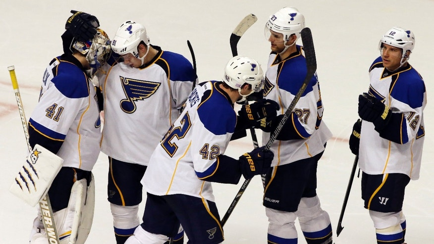 St. Louis Blues goalie Jaroslav Halak (41), left, celebrates with teammates after the Blues defeated the Chicago Blackhawks 3-2 during a shootout in an NHL hockey game in Chicago, Thursday, Oct. 17, 2013. (AP Photo/Nam Y. Huh)