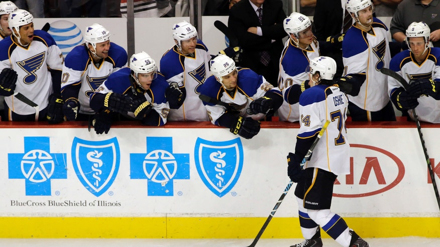 St. Louis Blues' T.J. Oshie (74) celebrates with teammates after scoring his goal against Chicago Blackhawks goalie Corey Crawford (50) during a shootout in an NHL hockey game in Chicago, Thursday, Oct. 17, 2013. The Blues won 3-2. (AP Photo/Nam Y. Huh)