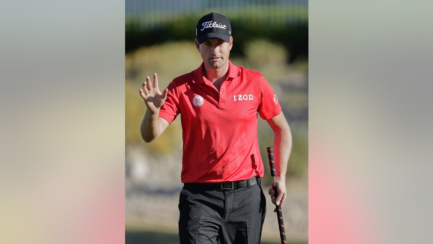 Webb Simpson waves briefly to spectators after sinking a putt for birdie on the 14th green in the second round of the Shriners Hospitals for Children Open golf tournament, Friday, Oct. 18, 2013, in Las Vegas. (AP Photo/Julie Jacobson)
