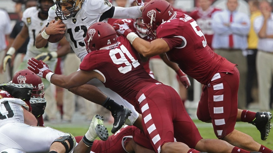 Army's quarterback Kelvin White (13) runs right up the middle through the Temple defense as Shahbaz Ahmed, (91) and Brandon Chudnoff, right, try to bring him down in the fourth quarter of an NCAA college football game Saturday, Oct. 19, 2013, in Philadelphia. Temple won 33-14. (AP Photo/Philadelphia Inquirer, Michael Bryant) PHIX OUT  NEWARK (N.J.) OUT  TV OUT  MAGS OUT
