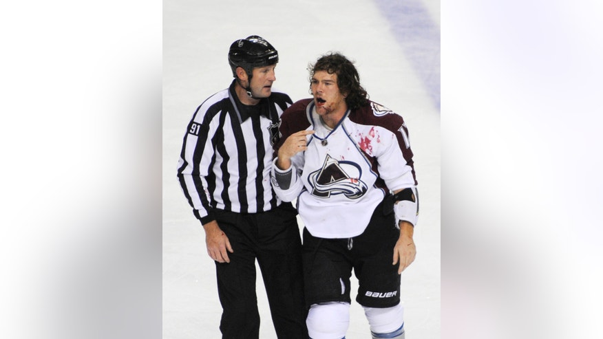 NHL linesman Don Henderson (91) skates Colorado Avalanche right winger Steve Downie to the penalty box after a fight with Buffalo Sabres' Mike Weber during the third period of an NHL hockey game in Buffalo, N.Y., Saturday, Oct. 19, 2013. Colorado won 4-2.  (AP Photo/Gary Wiepert)