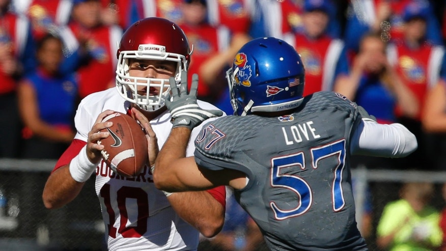 Oklahoma quarterback Blake Bell (10) looks for a receiver while pressured by Kansas linebacker Jake Love (57) during the first half of an NCAA college football game in Lawrence, Kan., Saturday, Oct. 19, 2013. (AP Photo/Orlin Wagner)