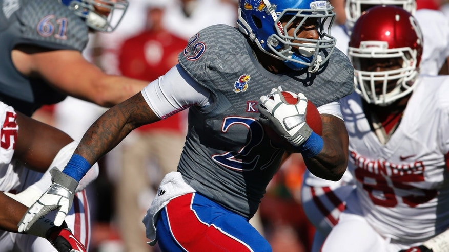 Kansas running back James Sims (29) breaks past Oklahoma defenders for a touchdown during the first half of an NCAA college football game in Lawrence, Kan., Saturday, Oct. 19, 2013. Sims scored on an 11-yard run. (AP Photo/Orlin Wagner)