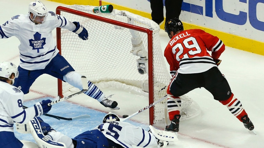 Chicago Blackhawks left wing Bryan Bickell (29) scores a goal past Toronto Maple Leafs goalie Jonathan Bernier (45) and defenseman Paul Ranger, top left, during the second period of an NHL hockey game Saturday, Oct. 19, 2013, in Chicago. (AP Photo/Andrew A. Nelles)