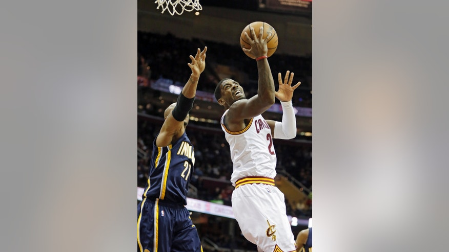 Cleveland Cavaliers' Kyrie Irving (2) shoots against Indiana Pacers' David West, left, in the first quarter of a preseason NBA basketball game Saturday, Oct. 19, 2013, in Cleveland. (AP Photo/Mark Duncan)