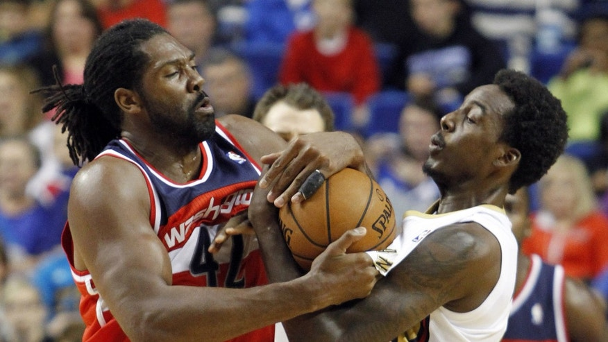 Washington's Nene Hilario, left, and New Orleans' Al-Farouq Aminu wrestle over a loose ball during the first quarter of an NBA basketball exhibition game on Saturday, Oct. 19, 2013, in Lexington, Ky. (AP Photo/James Crisp)