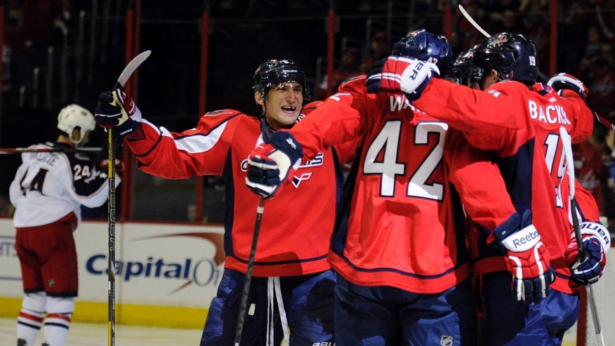 Washington Capitals right wing Alex Ovechkin, left, of Russia, celebrates teammate Joel Ward's (42) goal during the second period an NHL hockey game against the Columbus Blue Jackets, Saturday, Oct. 19, 2013, in Washington. (AP Photo/Nick Wass)