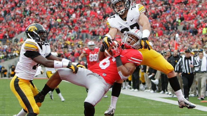 Iowa defensive backs Desmond King, left, and John Lowdermilk, right, break up a pass intended for Ohio State wide receiver Evan Spencer, center, during the second quarter of an NCAA college football game Saturday, Oct. 19, 2013, in Columbus, Ohio. (AP Photo/Jay LaPrete)