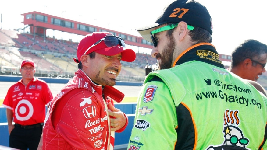 Alex Tagliani, left, of Canada, talks with James Hinchcliffe, of Canada, on pit road, waiting to qualify for Saturday's IndyCar auto race at Auto Club Speedway, Friday, Oct. 18, 2013, in Fontana, Calif. (AP Photo/Alex Gallardo)