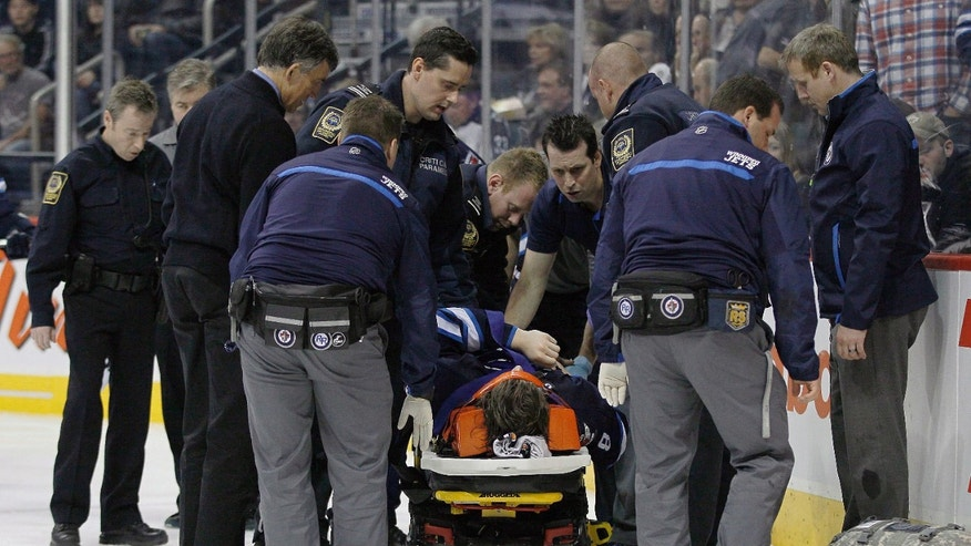 Winnipeg Jets' Jacob Trouba (8) is attended to by paramedics after crashing head first into the boards during the second period of an NHL hockey game, Friday, Oct. 18, 2013 in Winnipeg, Manitoba.  (AP Photo/The Canadian Press, John Woods)