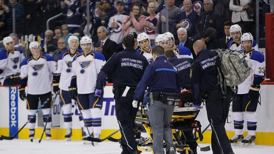 Winnipeg Jets' Jacob Trouba (8) is taken off the ice by paramedics after crashing head first into the boards during the second period of an NHL hockey game, Friday, Oct. 18, 2013 in Winnipeg, Manitoba.  (AP Photo/The Canadian Press, John Woods)