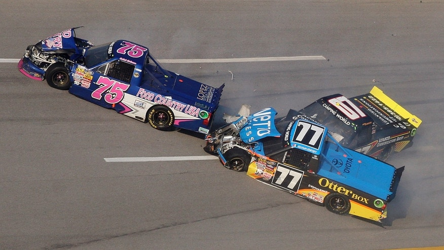 Caleb Holman (75), German Quiroga (77) and Chris Cockrum (07) collide in Turn 3 during the NASCAR Camping World Truck Series race at the Talladega Superspeedway in Talladega, Ala., Saturday, Oct. 19, 2013. (AP Photo/Dale Davis)